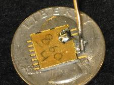 Packaged radiation sensor device placed on a quarter for size comparison